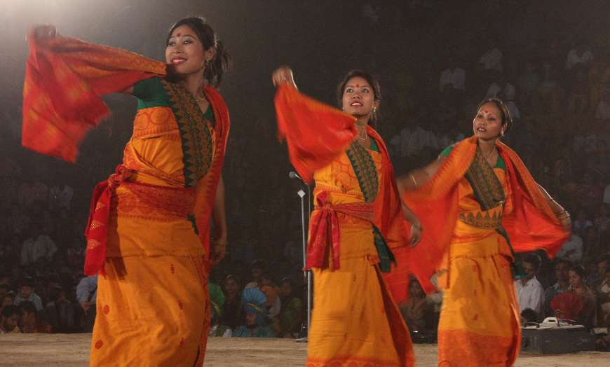 Three women in traditional saffron clothes dancing during Bihu in Assam, north east India