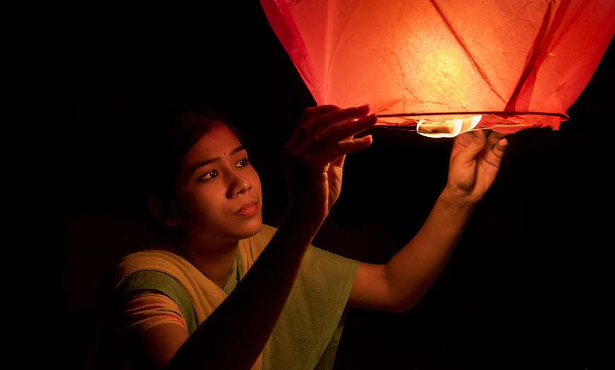 Indian woman in traditional clothing holding an illuminated lantern during Diwali