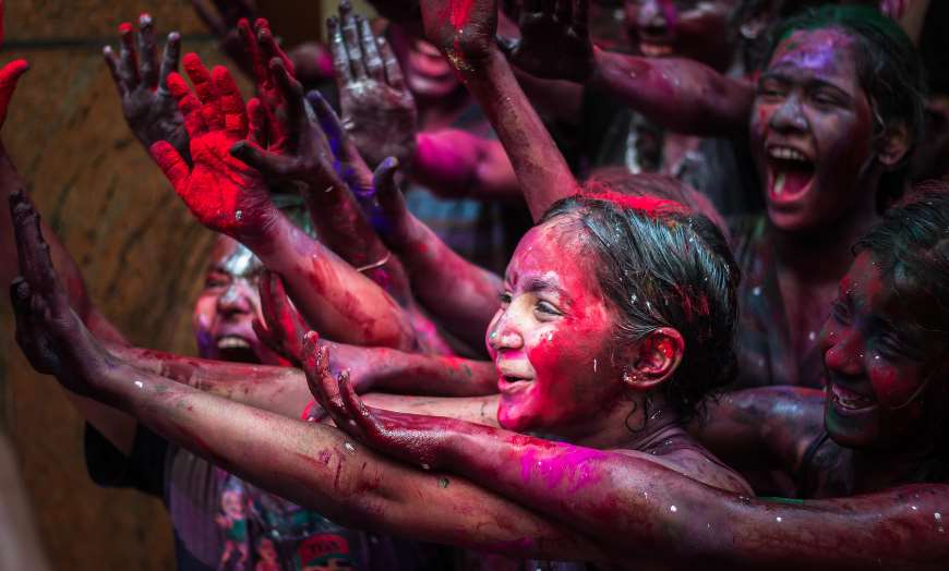 Youngsters covered in colourful paints and powders celebrating the Holi Festival in India