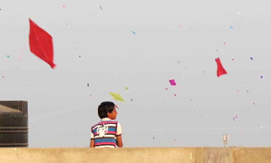 Young boy on a rooftop wearing a striped shirt watching hundreds of kites flying in the sky during the International Kite Festival in Gujarat, India