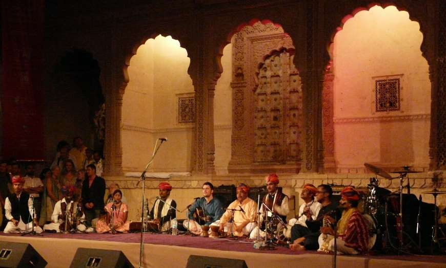 Folk musicians playing traditional instruments on stage at the Jodhpur RIFF festival in Rajasthan, India
