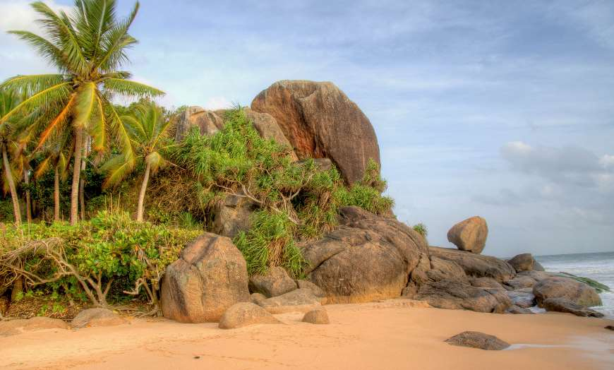 Large rocks on a sandy beach in Induruwa, Sri Lanka