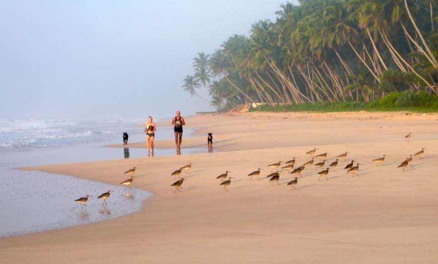 Two people running on the beach in Kogala, Sri Lanka