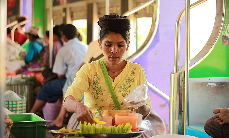 Woman serving traditional food on a local train in Burma