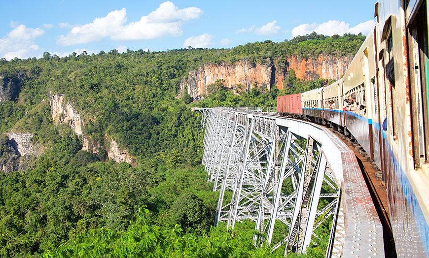 Train crossing an old metal viaduct in Burma
