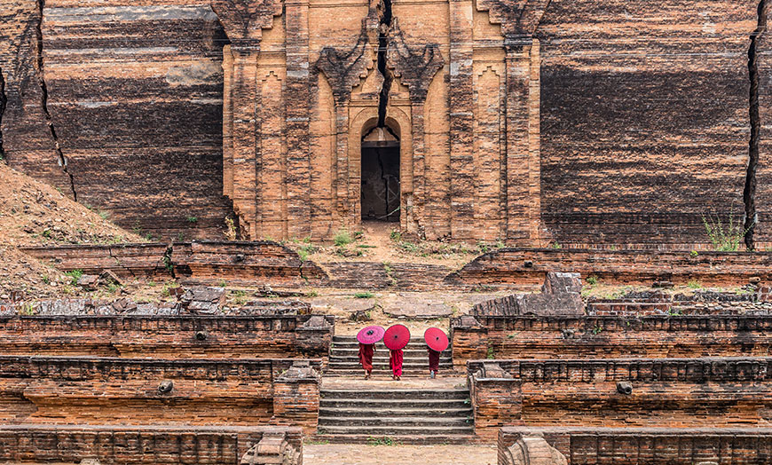 Three monks climbing steps towards the entrance of a pagoda in Burma