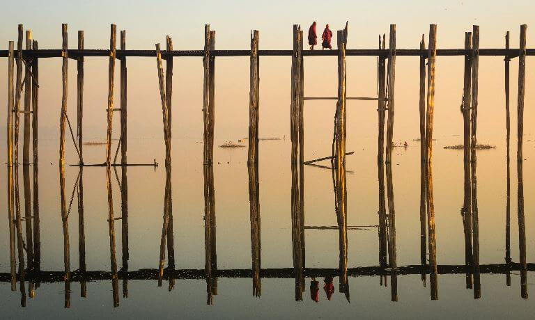 Two monks walking on a wooden bridge at sunset