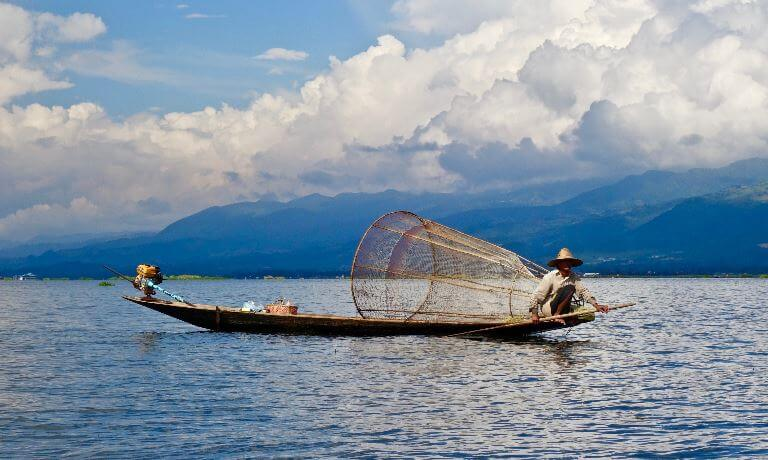 Fisherman on a small wooden boat in Burma