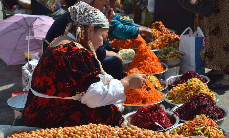 Woman in traditional clothing surrounded by her produce at the Siyob Bazaar in Samarkand, Uzbekistan