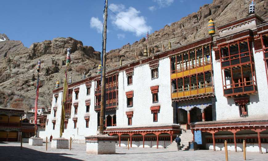 White-washed Hemis Monastery surrounded by prayer flags in Ladakh