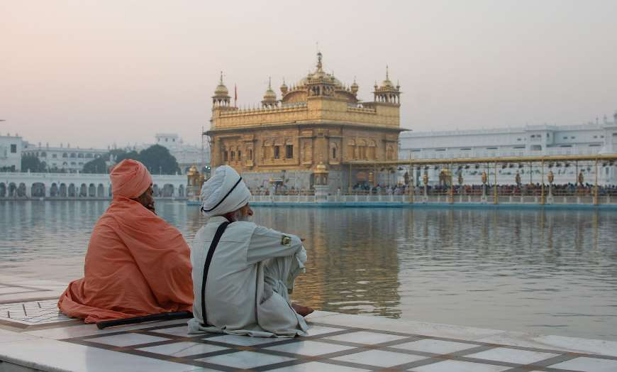 Two Sikh men sitting and looking at the Golden Temple in Amritsar at dusk