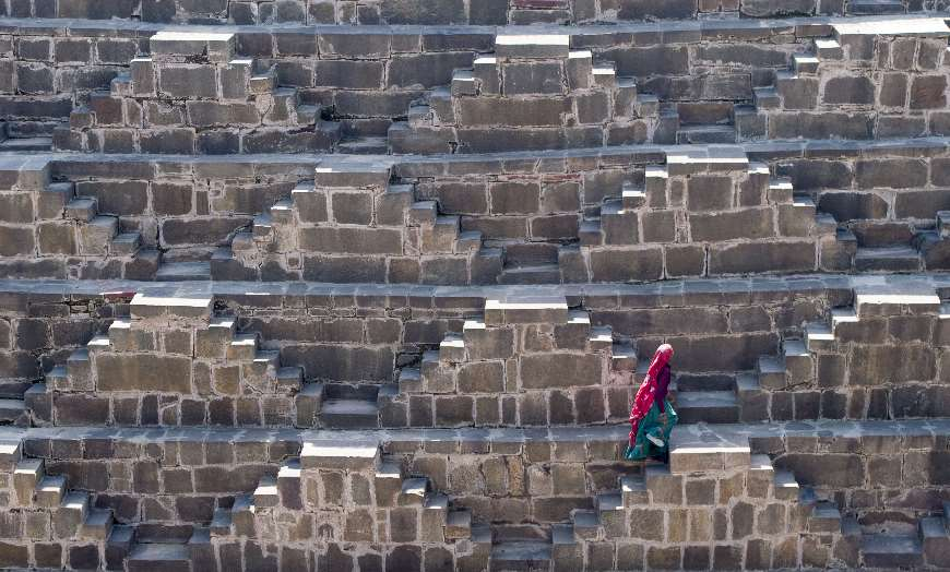 Lady in a red and green sari climbing the stairs of the Chand Baori stepwell in Abhaneri, Rajasthan