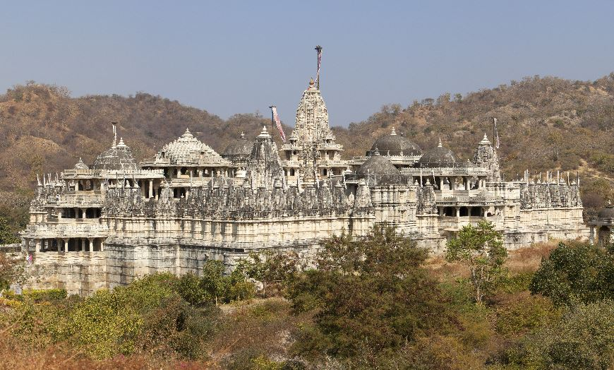 White marble temple surrounded by forested hills in India