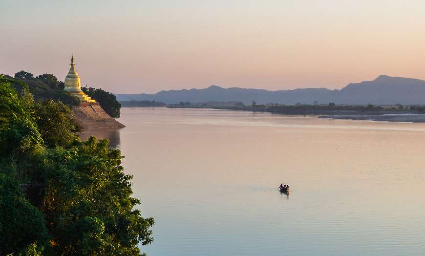 Small boat sailing on the serene Irrawaddy River at sunset in Bagan, Burma