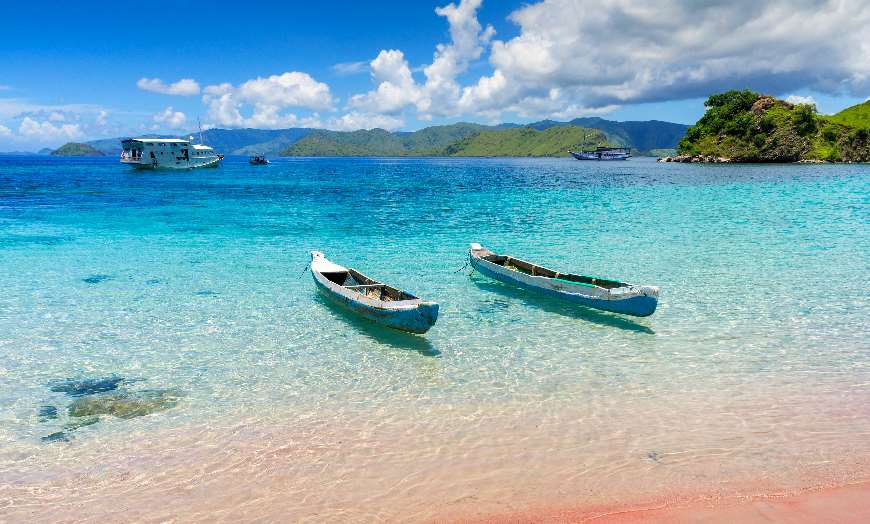 Two wooden boats floating on the turquoise waters of Komodo National Park, Indonesia