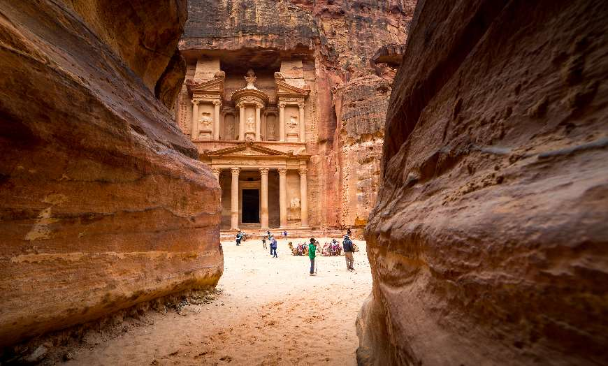 View through a narrow passage in the rock to the Treasury in Petra, Jordan