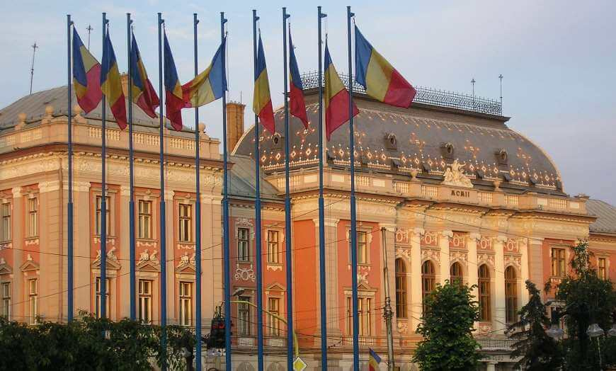Romanian flags flying outside of a building in Cluj Napoca