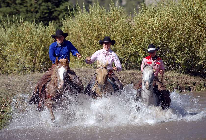 Three cowgirls on horses in river in USA