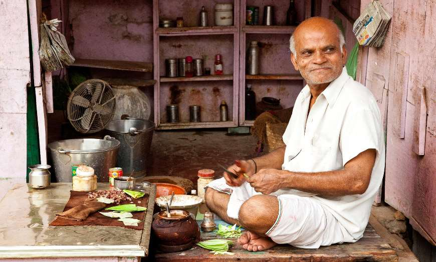 Man sitting at his stall in a market in India