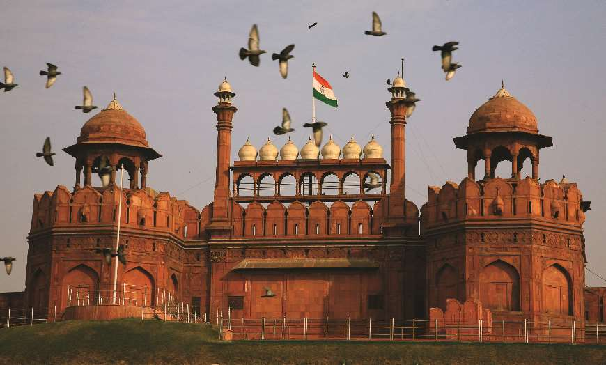 Birds flying over the towering walls of Delhi's Red Fort