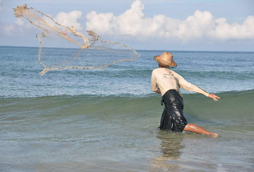 Ngwe Saung fisherman throwing his fishing net into the sea