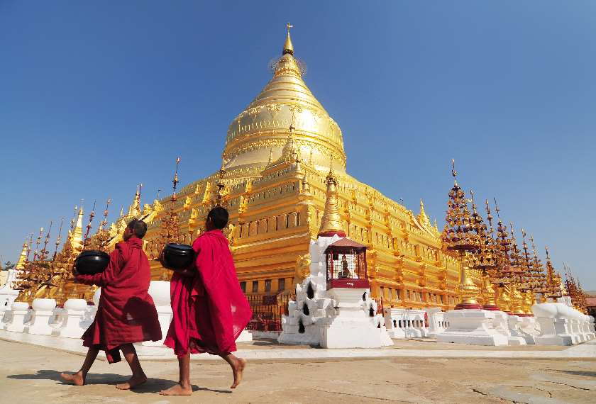 Two young monks in red walking past the golden edifice of Shwedagon Pagoda in Yangon