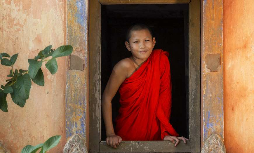 Young novice monk in a red robe at a temple window in Burma