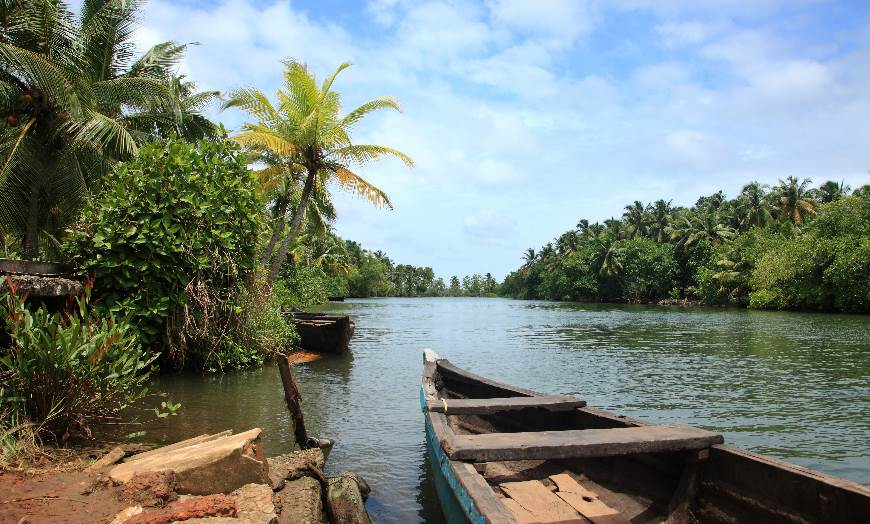 Wooden boat on the palm-lined backwaters in Kerala, India