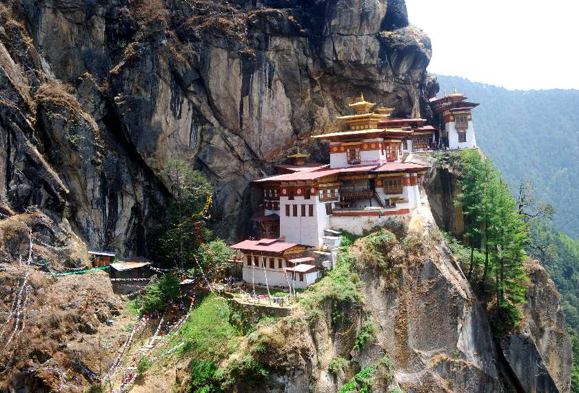 View of the Tiger's Nest Monastery clinging to the side of a cliff in Bhutan