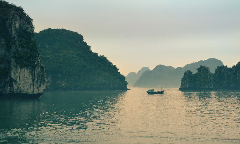 Small fishing boat surrounded by towering limestone rocks and islets in Ha Long Bay