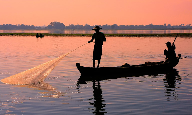 Two people fishing in a river in Myanmar from a small wooden boat at sunset