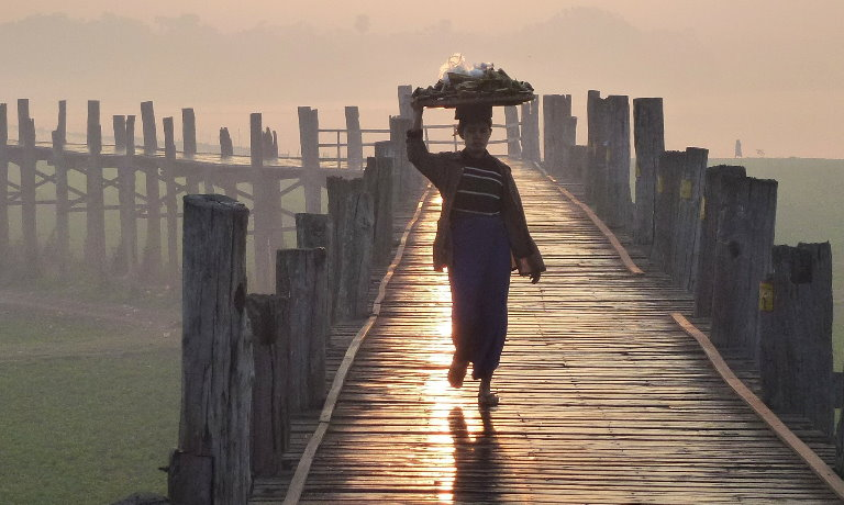 Person walking towards the camera on an ancient wooden bridge in Mandalay