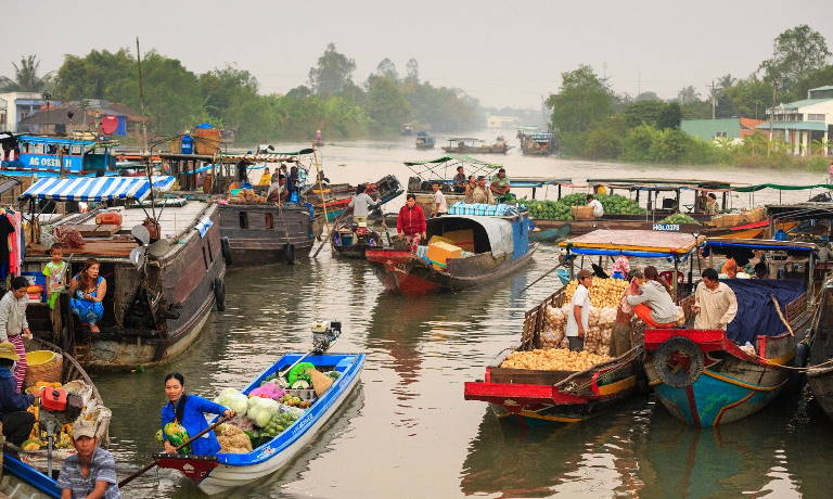 Busy floating market with people selling their wares in the Mekong Delta