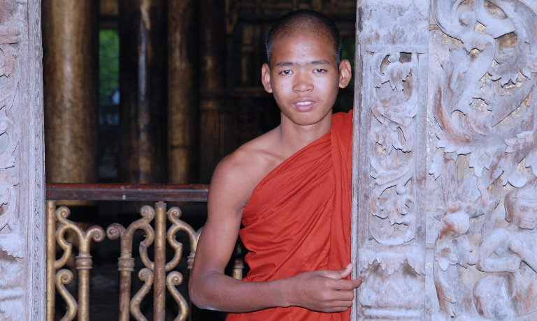 Male monk in saffron robe smiling at the camera in Myanmar