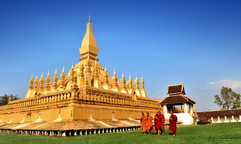 Group of monks in scarlet robes walking past a golden temple stupa in Laos