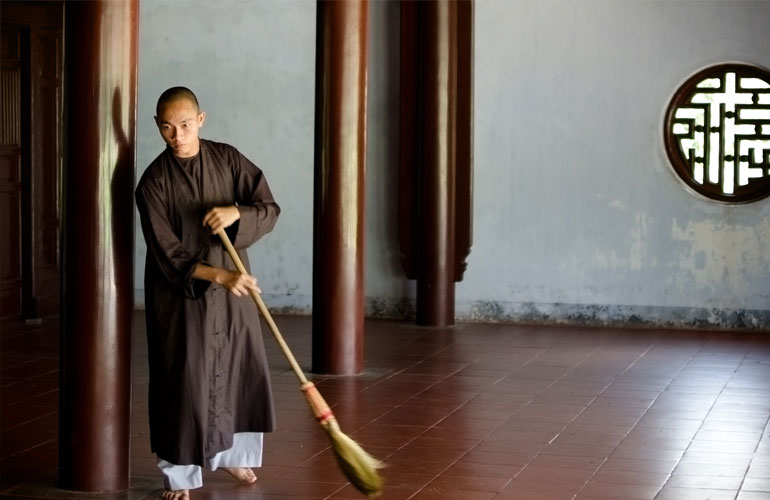 Monk sweeping a temple in Hue