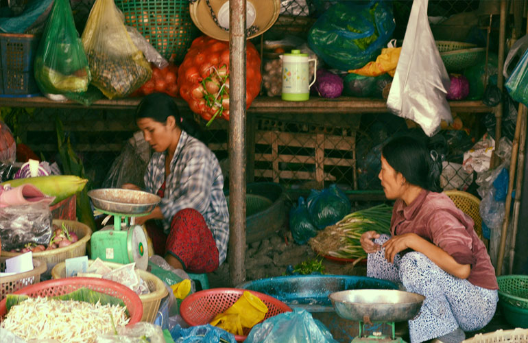 Market traders in Vietnam surrounded by produce