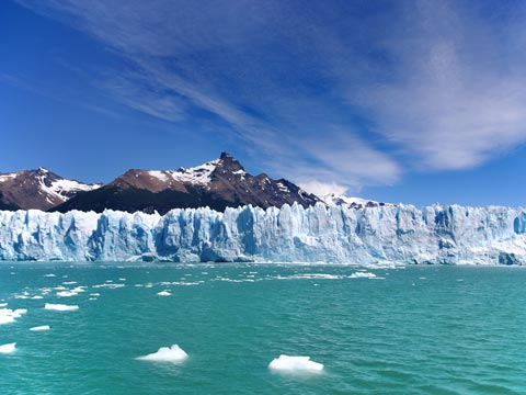 Vast aqua-blue glacier with mountain backdrop