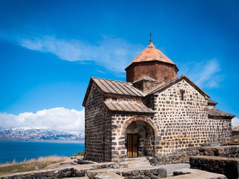 Ancient stone church overlooking the dark blue Lake Sevan in Armenia
