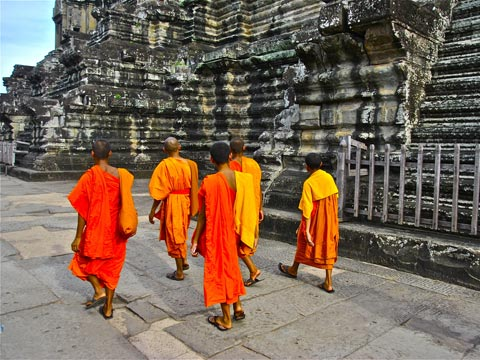 Five monks in bright saffron-coloured robes walking past the great stone temples of Angkor Wat in Cambodia