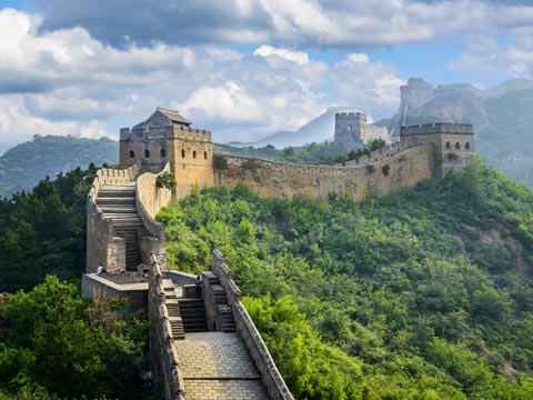Great stone bastions of the Great Wall of China surrounded by thickly forested hills