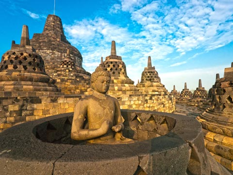 Seated Buddha and stone Stupas of the Borobudur temple complex at Yogyakarta in Java