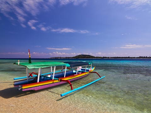 Multi-coloured boat on a sandy beach in the Gili Islands with hills in the background