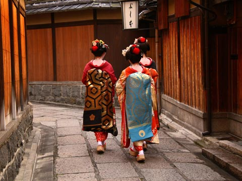 Three colourfully dressed geishas walking through an old lane in Kyoto, Japan