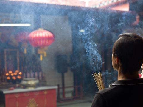 Person holding lit incense sticks praying at a temple in Malaysia