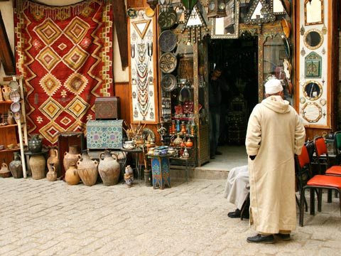 Man in skull-cap and traditional Moroccan clothing in a bazaar in Morocco
