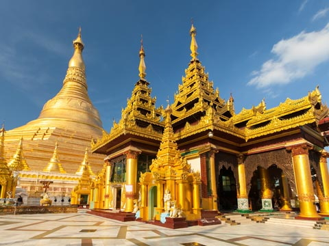Small shrines and main central stupa of the opulent and golden Shwedagon Pagoda in Yangon