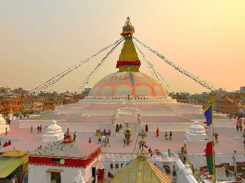 Large white dome of Stupa with prayer flags and pilgrims, Kathmandu