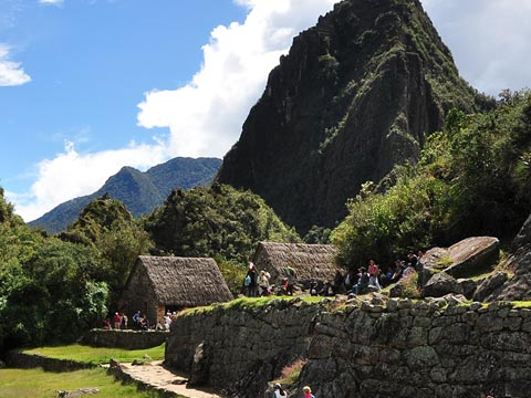 Traditional Peruvian thatched buildings surrounded by thickly forested hills