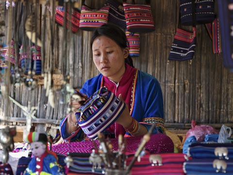 Karen woman in traditional red and blue clothing at a market stall in Thailand